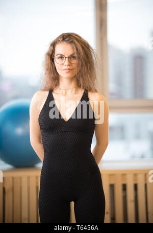Young pretty woman in glasses in the fitness studio - Stock Image