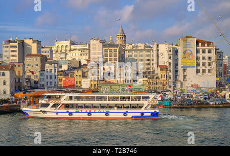 Ferry arriving at Karakoy (Turyol) station at bottom of Galata area.  View of river, and residential area in background, capture from Galata bridge.   - Stock Image