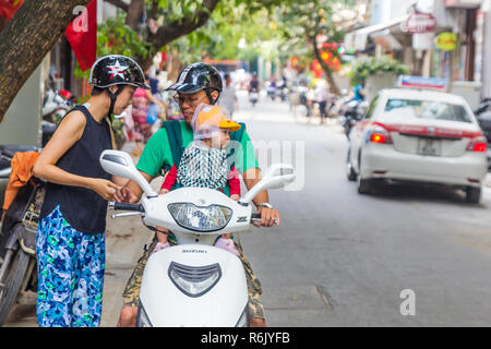 Hanoi, Vietnam - CIRCA October 2015: woman, man in helmets, child in baby carrier and yellow cap travel on scooter in Hanoi, Vietnam - Stock Image