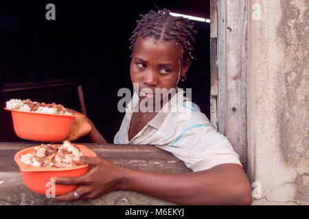 Floods in Mozambique  March 2000; A young woman hands out cooked bowls of rice and stew made with relief supplies - Stock Image