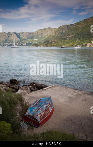 An old, weathered rowing boat on the coast of Cavtat, Croatia - Stock Image