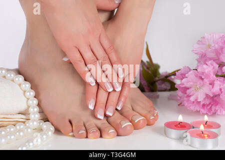 Female feet and hands with french nail polish in spa salon with decorative pink flower, candles, pearls and towel. Girl pedicure and manicure concept - Stock Image