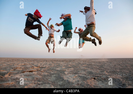 Botswana, Makgadikgadi. A family jump high in the air above the Makgadikgadi salt pans. MR. - Stock Image