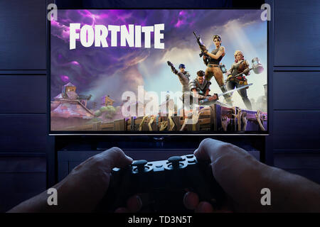With Playstation controller in hand, a man prepares to play Fortnite: Save the World as the intro loading screen in seen on a TV (Editorial use only). - Stock Image