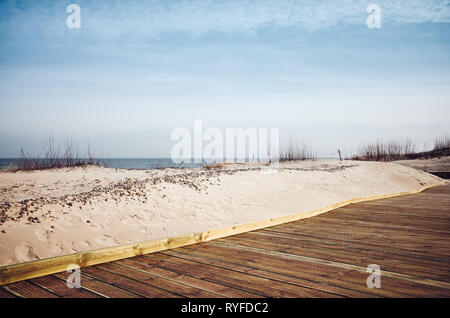 View of a wooden boardwalk by a beach, color toned picture. - Stock Image