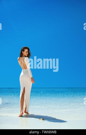 Elegant brunette woman walking on a tropical beach - Stock Image