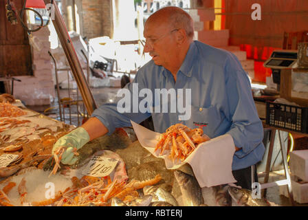 Italy, Venice, fish market, the seller weighs crabs. - Stock Image