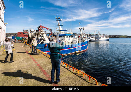 Killybegs, County Donegal, Ireland. 28th March 2019. Tourists take photos of fishing boats in the harbour on a fine, warm day on the north-west coast. Credit: Richard Wayman/Alamy Live News - Stock Image