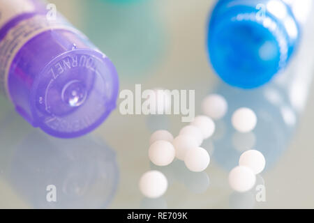 Homeopathic globules scattered around with their colored containers in the shape of tube - Stock Image