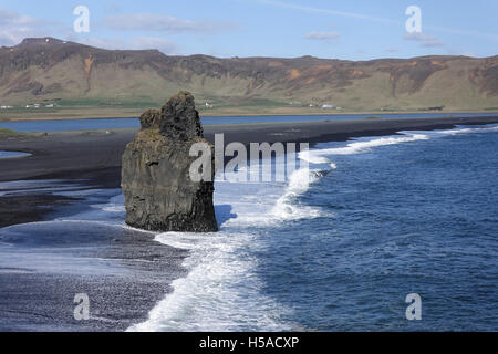 Iceland :Rock formation on beach of volcanic sand - South coast - Stock Image