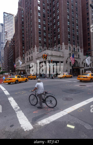 Man in a bicycle waiting for green traffic light in Lexington Avenue and E48 st, Manhattan, New York, USA - Stock Image