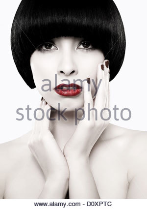 Young woman with black bob touching face - Stock Image
