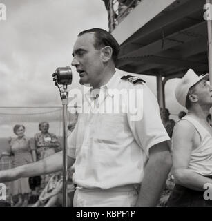1950s, historical, a male officer out on the deck on a union-castle steamship standing making an announcement to passengers at the microphone, - Stock Image