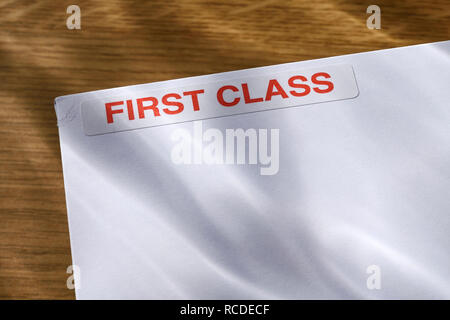 A First Class sticker on a white envelope - Stock Image