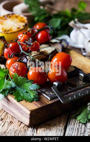 Summer vegetables platter, fresh seasonal snack with roasted cherry tomatoes, eggplant, zucchini, lemon on rural wooden board, vegan plant based food, - Stock Image