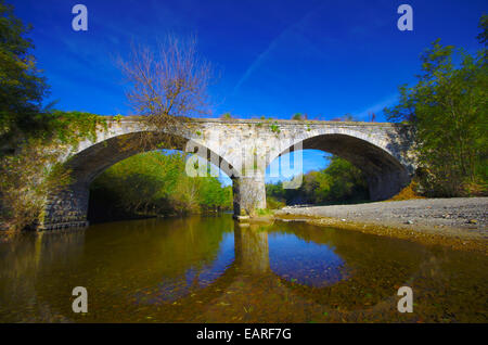 Abandoned stone bridge over a small river. - Stock Image