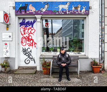 Senior elderly man sitting on a bench outside a veterinary practice in  Mitte, Berlin - Stock Image