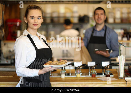 Young woman and man working in a restaurant. Kitchen behind - Stock Image