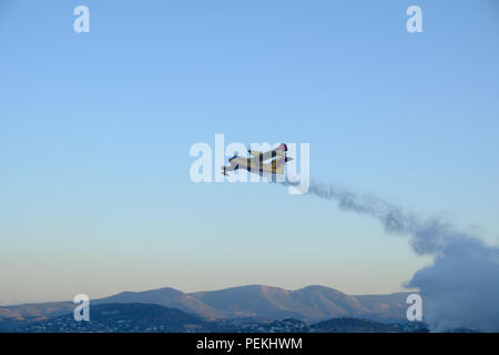 Emergency fire service aeroplane spraying water preventing the fire from spreading further on the mountains of Saronida, East Attica, Greece, Europe. - Stock Image
