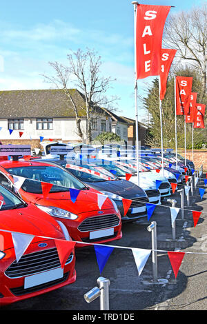 Sale poster at Ford car dealership business on forecourt display used second hand red white & blue cars bunting & sales promotion banners England UK - Stock Image