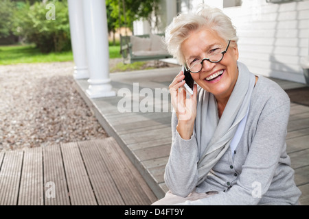 Woman talking on cell phone on porch - Stock Image