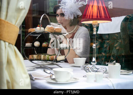 Vintage, beautiful woman in red afternoon tea dress enjoying afternoon tea in train carraige with cakes, sandwiches and tea - Stock Image