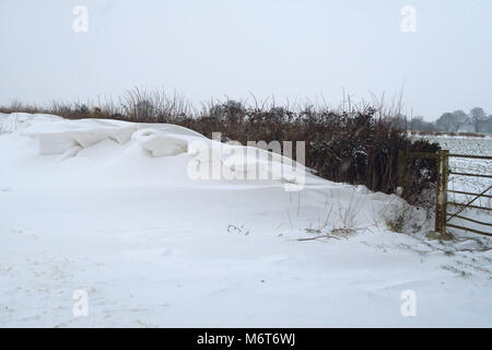 Snow drifts on road towards the Firs Garage after a March snowfall, Hook Norton, Oxfordshire - Stock Image