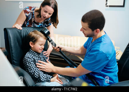 Paediatrician Doctor Doing Brain Treatment To Autistic Child In Clinic - Stock Image