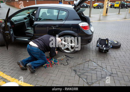 Elderly man kneeling beside his car preparing to change the rear wheel with its punctured tyre in a town centre - Stock Image