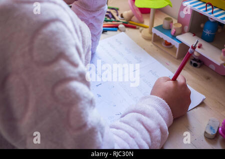 6 years old child girl doing writing homework in her room. Kids learn to write concept - Stock Image
