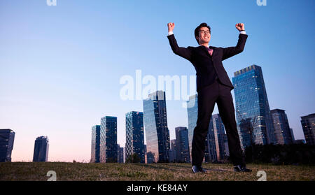 Businessman standing raising his hands against skyscrapers in city at sunset - Stock Image