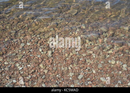 Rippling shallow water with brown stones and pebbles below the surface - Stock Image