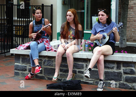 Three girls playing ukuleles and singing as they relax at the Old Town pedestrian mall, Winchester, Virginia - Stock Image