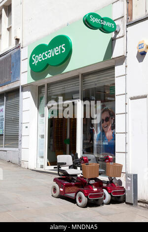 Mobility scooters parked outside Specsavers, Bradford, West Yorkshire - Stock Image