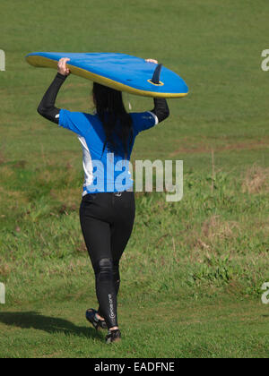 Young woman carrying a surfboard on her head, Bude, Cornwall, UK - Stock Image