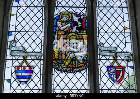 Stained glass window, St Peter's church, Harrold, Bedfordshire, UK; it shows two shoemakers at work and is dedicated to St Crispin. - Stock Image