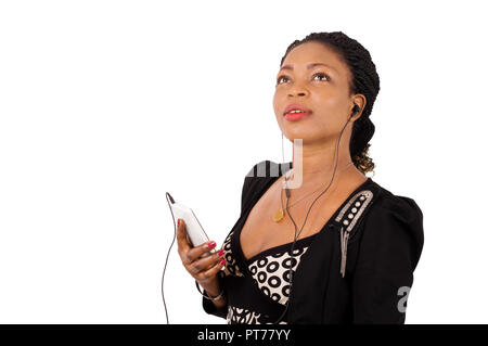 Young woman using a cell phone with headphones on white background - Stock Image