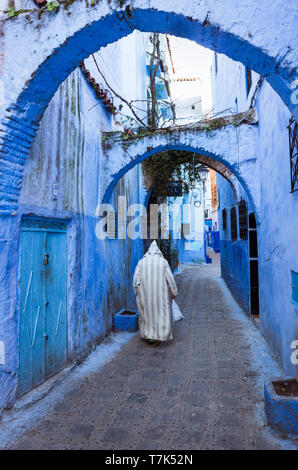 Chefchaouen, Morocco : A senior man wearing a traditional djellaba walks in the blue-washed alleyways of the medina old town. - Stock Image