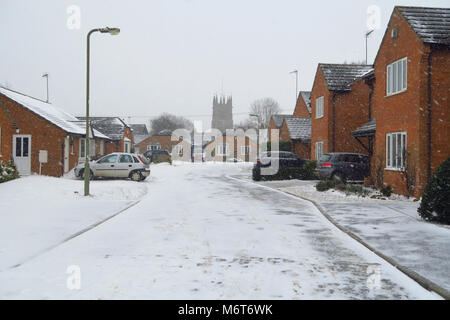 The Shearings and St Peter's Church after a March snowfall in the north Oxfordshire village of Hook Norton - Stock Image