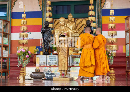 Two young Buddhist monks wearing orange robes admiring gilt statues in a shrine in Phnom Penh, Cambodia. - Stock Image