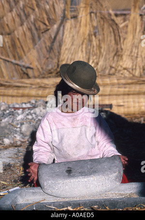 Uros Indian Girl, Grinding Corn with a Large Stone to Make Flour, Lake Titicaca, Peru, South America - Stock Image