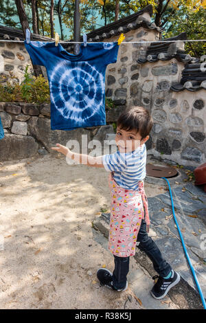 A young boy proudly poses with the t-shirt that he has tie dyed and is hanging outside on a washing line to dry. - Stock Image
