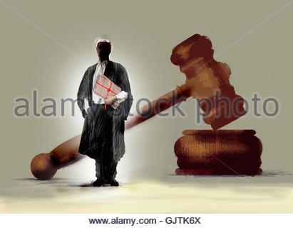 Barrister holding legal documents in front of large gavel - Stock Image