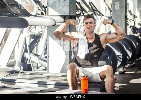 Portrait of successful athlete handsome masculine man sitting during treadmill exercise in gym, tired sportsman drinking water in sports hall. indoor, - Stock Image