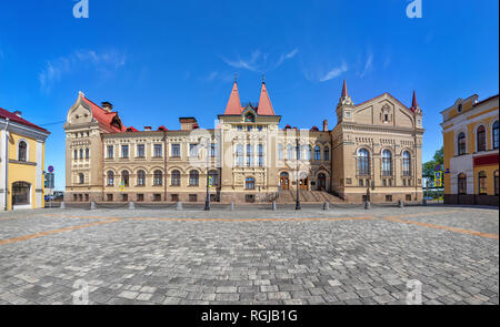 Rybinsk, Russia. Red square and exterior of historic building - former grain exchange in russian revival style - Stock Image