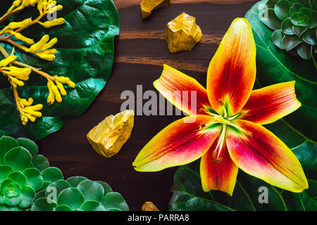 Yellow Lily with Yellow Jasper and Mixed Botanicals on Wood Table - Stock Image