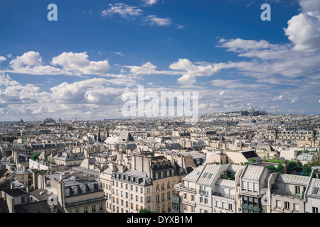 View of the Paris rooftops with Sacre Coeur Basilica in the distance in the city of Paris, France. - Stock Image