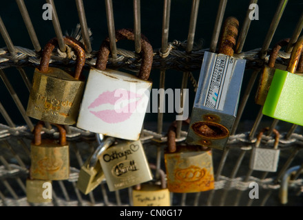 Padlocks on bridges over the River Seine in Paris, usually attached by lovers to symbolise their togetherness - Stock Image