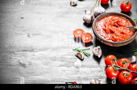 Tomato sauce with garlic and herbs. On black background. - Stock Image