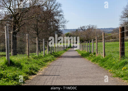 A long tarmac footpath with tall fence posts to both sides. - Stock Image
